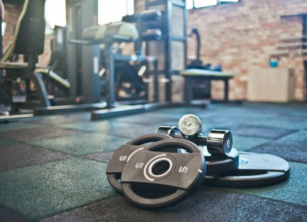 巴伯, 啞鈴躺在健身房的背景下的地板上。免費的重量訓練。功能強大的培訓 - 健身房 個照片及圖片檔