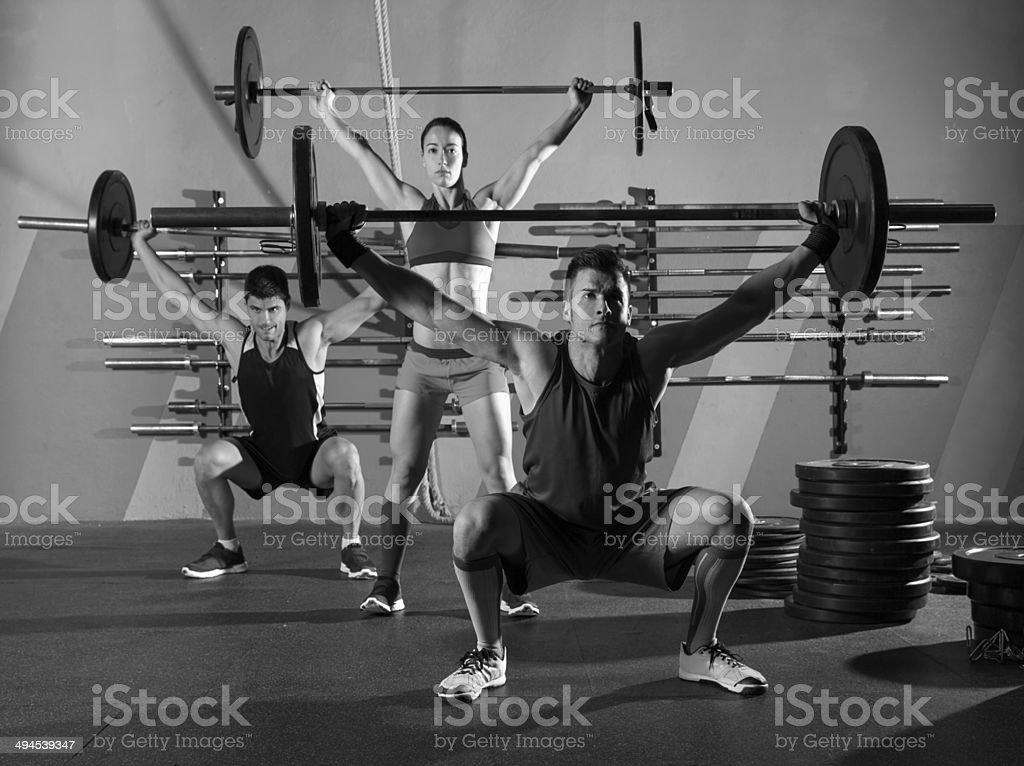 Barra para pesas grupo de levantamiento de peso de ejercicios en el gimnasio - Foto de stock de 20 a 29 años libre de derechos
