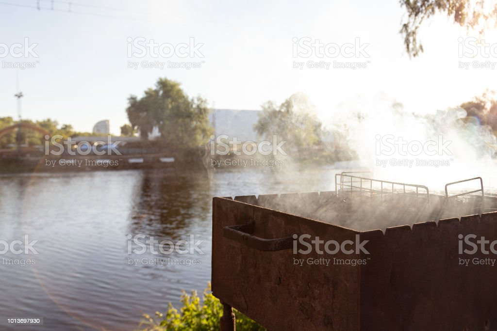 Barbeque brazier with heavy smoke during grilling meat. BBQ outdoor party near lake or river. Copuspace