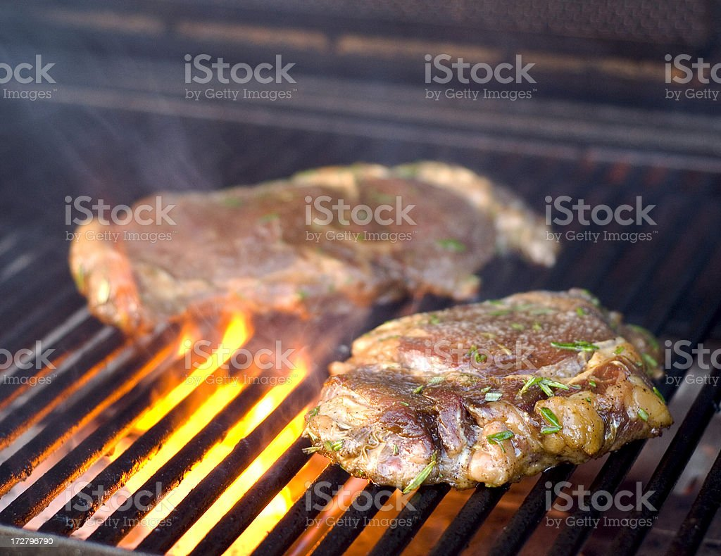 Barbeque Ribeye Steaks with Flame Cooking on the Grill royalty-free stock photo