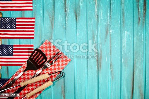 470765518istockphoto Barbeque utensils on checked cloth. USA flags. Blue wooden background. 470765518