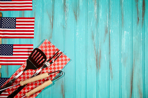 Barbeque utensils on checked cloth. USA flags. Blue wooden background. stock photo