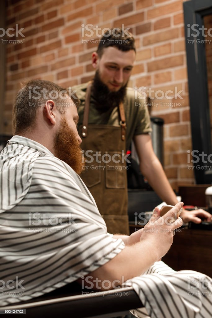 Barber and bearded man in barber shop - Zbiór zdjęć royalty-free (Akcesorium osobiste)
