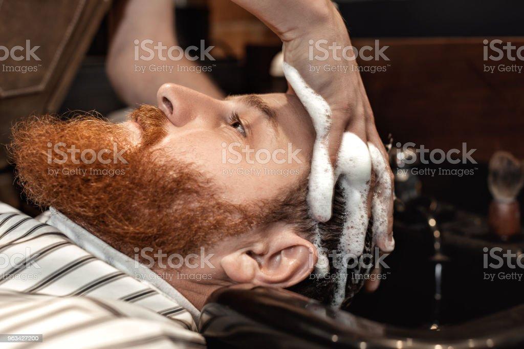 Frisör och skäggig man i frisersalong - Royaltyfri Affär Bildbanksbilder