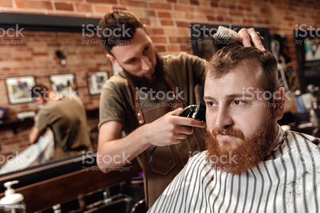 Fryzjer i brodaty mężczyzna w salonie fryzjerskim - Zbiór zdjęć royalty-free (Akcesorium osobiste)