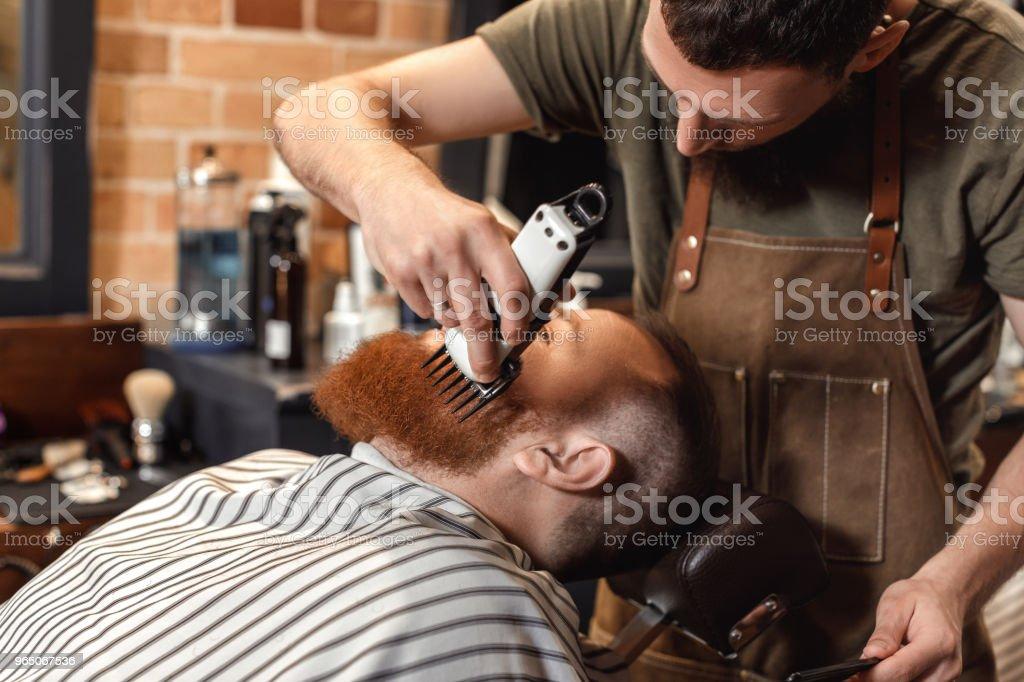 Barber and bearded man in barber shop zbiór zdjęć royalty-free