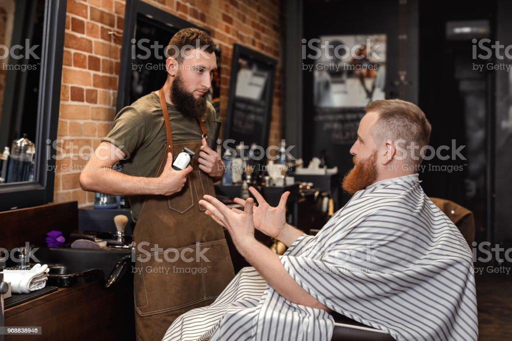 Barbero y barbudo en peluquería - foto de stock