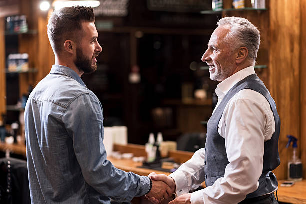 Barber and client shaking hands stock photo