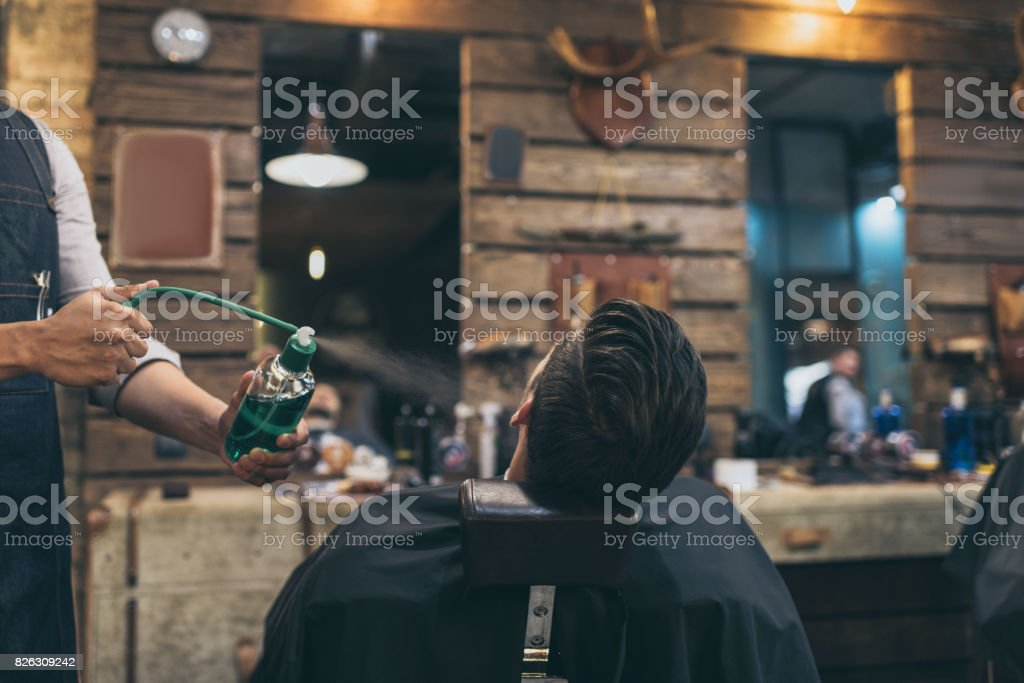 barber applying perfumes to customer stock photo