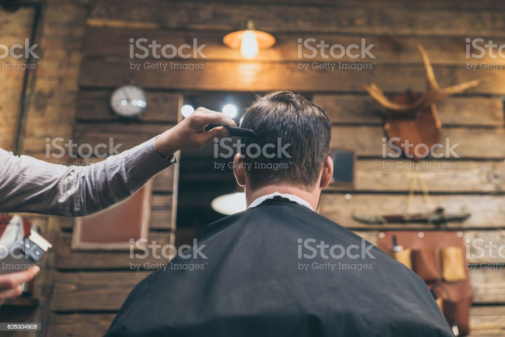 barber combing hair of customer stock photo