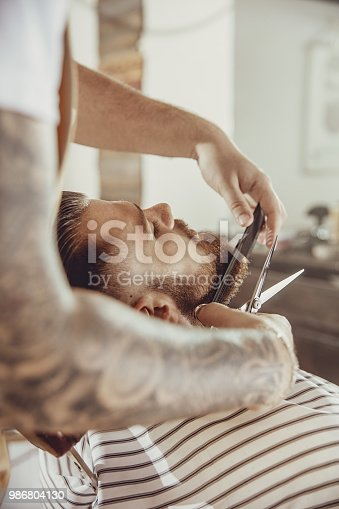 986804130istockphoto Barber cuts the client's beard with scissors and a comb 986804130
