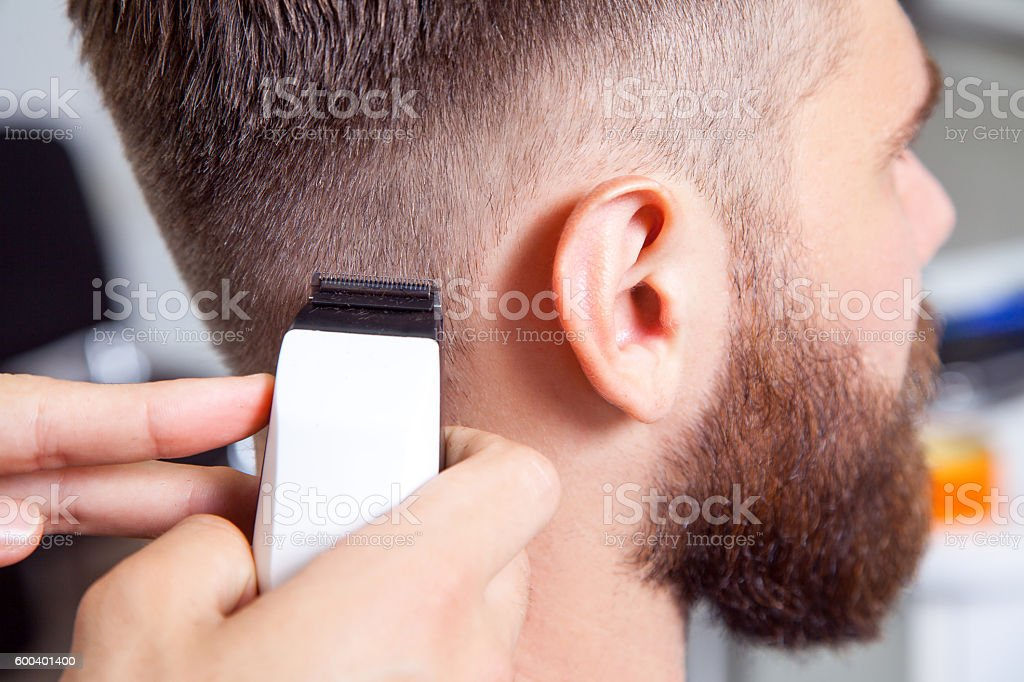 Barber cutting and modeling hair by electric trimmer stock photo