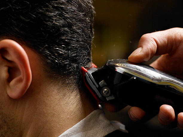 Barber cutting man's hair, close-up of electric razor, side view stock photo