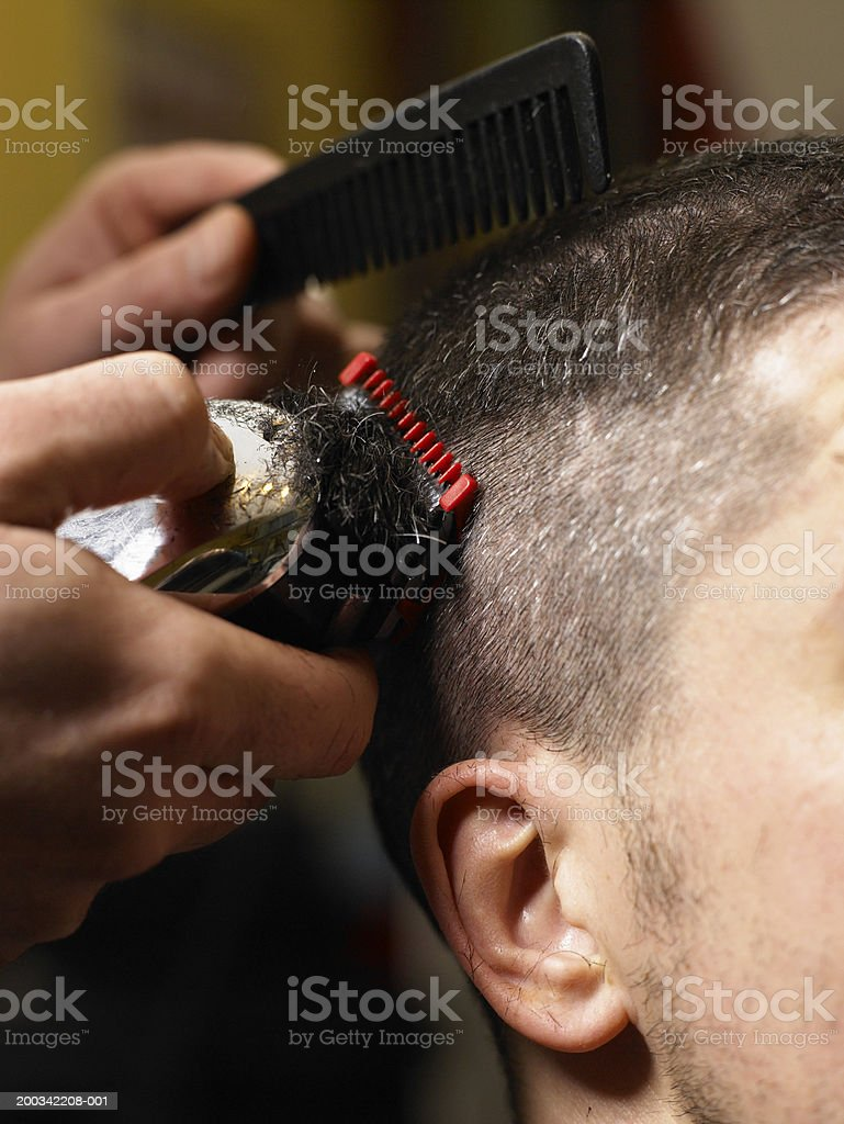 Barber cutting man's hair with electric razor, close-up of hands stock photo