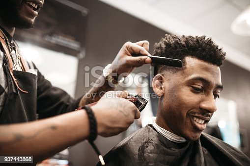 An African American man gets his hair cut by a skilled stylist at a small business barbershop.