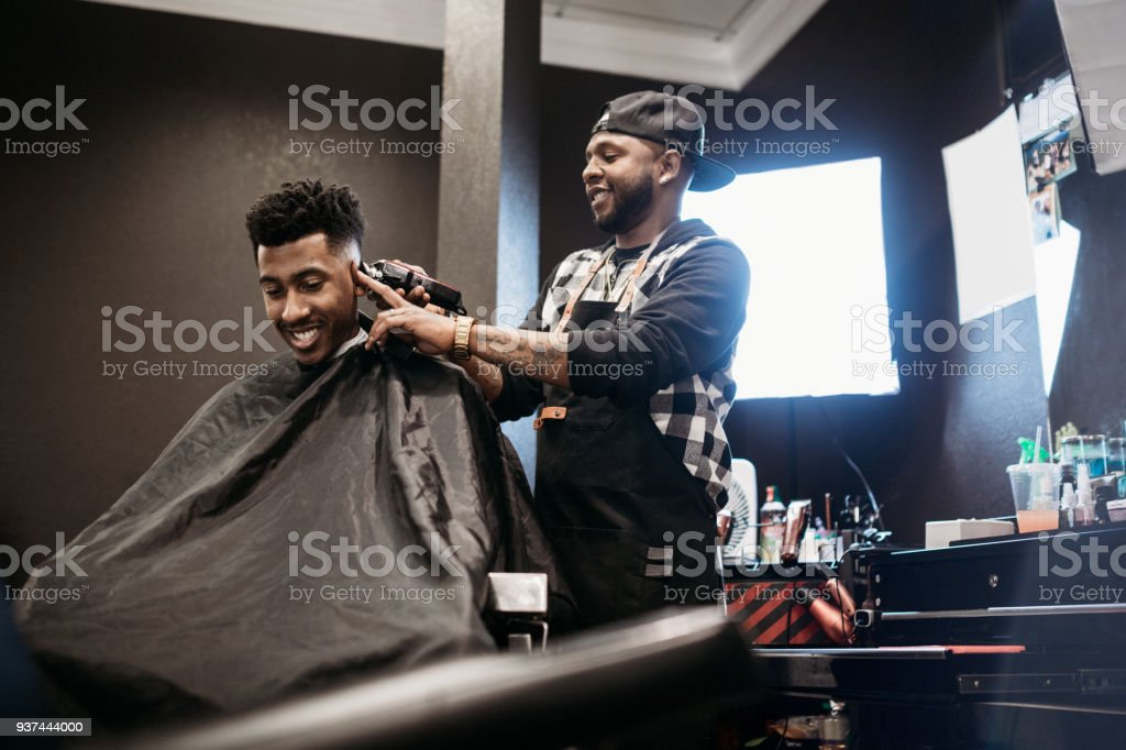 Barber Giving A Haircut in His Shop stock photo