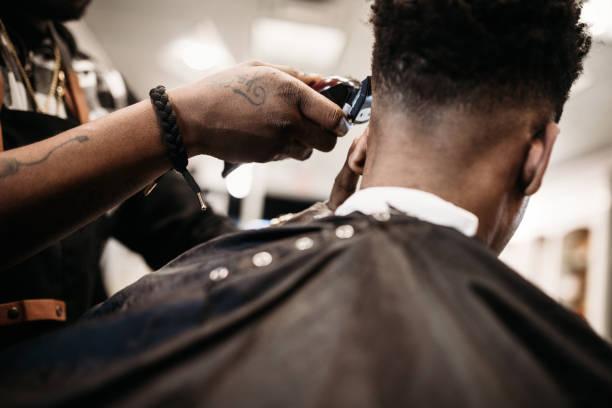 geben einen neuen haarschnitt in seinem geschäft barber - männerfrisuren stock-fotos und bilder