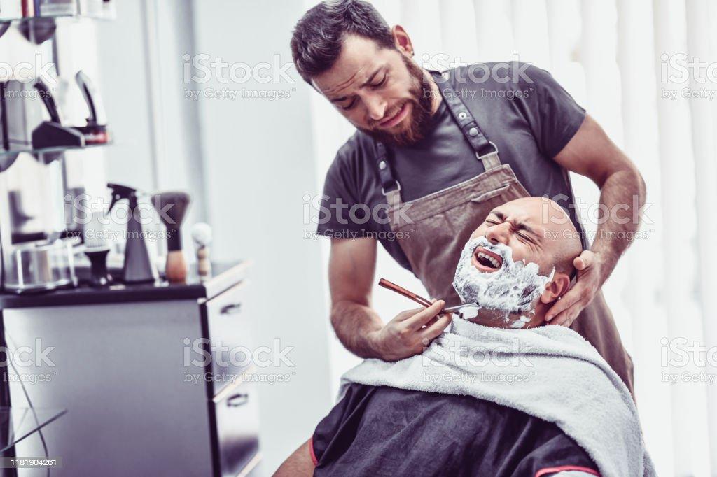 Barber macht einen Fehler und schneidet männlichen Kunden mit Rasiermesser - Lizenzfrei Altertümlich Stock-Foto