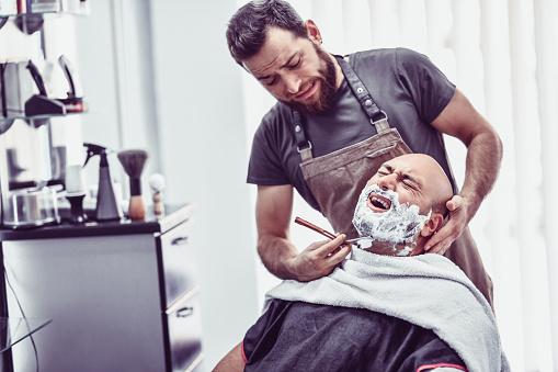 Barber Macht Einen Fehler Und Schneidet Männlichen Kunden Mit Rasiermesser Stockfoto und mehr Bilder von Altertümlich