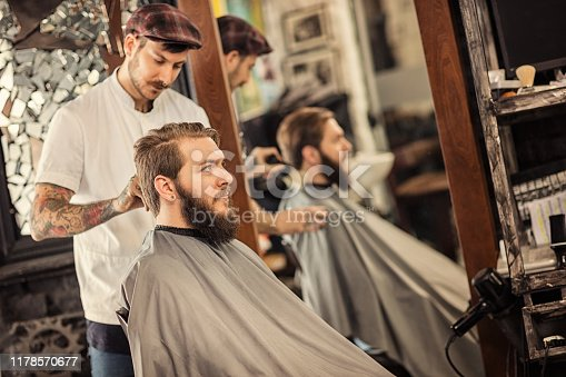 928445950 istock photo Barber man grooming with scissors of real hipster 1178570677