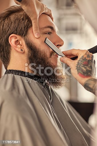 928445950 istock photo Barber man grooming with scissors of real hipster 1178573641