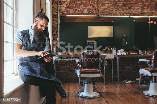 istock Barber organizing his business using digital tablet 643977234