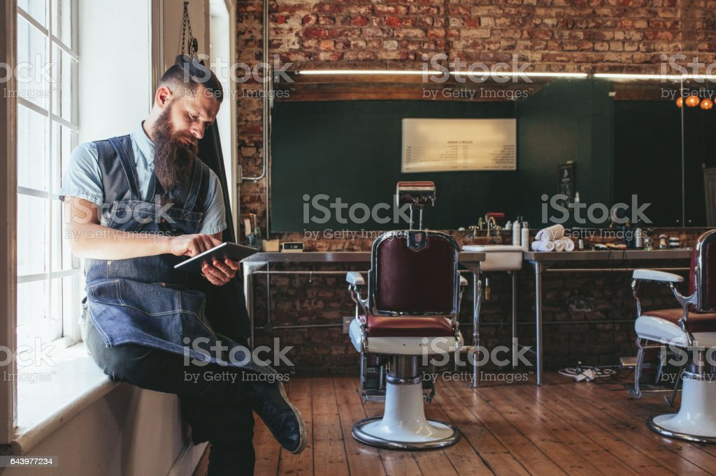 Barber organizing his business using digital tablet stock photo