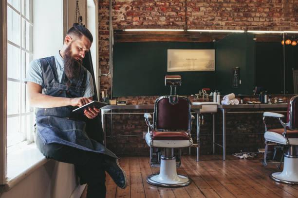 barber, organiser son entreprise à l'aide de tablette numérique - barbier coiffeur photos et images de collection