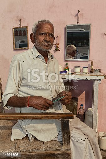 An Indian barber sits in his barber chair holding his scissors that he uses on his patrons. His shop is located on the sidewalk in Delhi, India. (Image is toned)