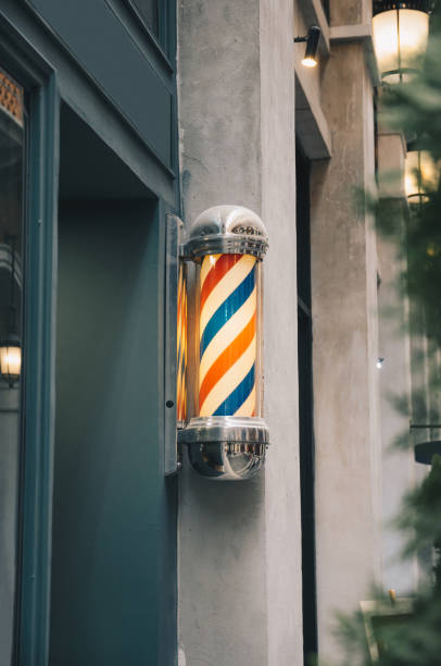 barber pole on grey wall with green wooden barber shop stock photo