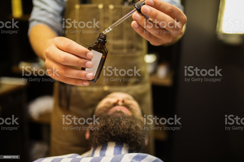 Barber putting beard oil to client stock photo
