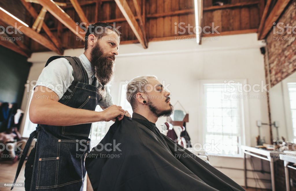 Barber serving client in hair salon stock photo
