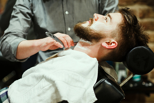 Barber shaving a bearded man stock photo