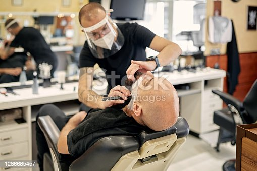 Socially responsible salon professional wearing protective face mask and shield as he uses straight edge razor to shave bearded client.