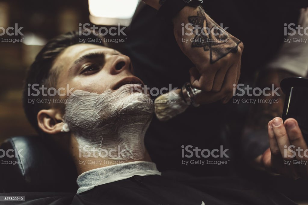 Barber shaving client stock photo