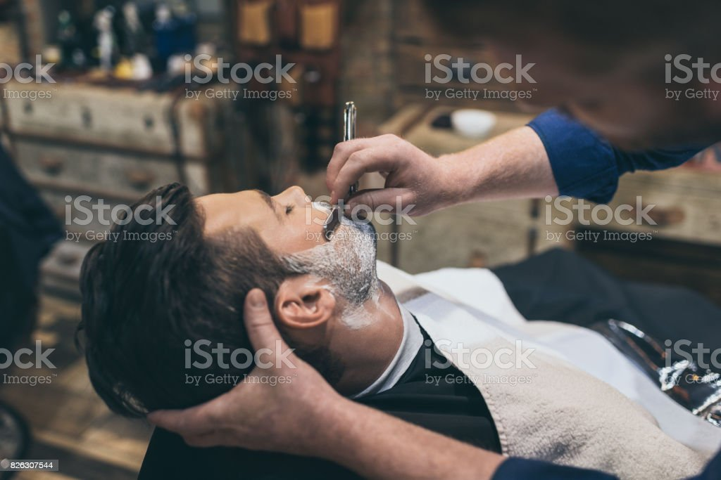 Barber shaving customer stock photo