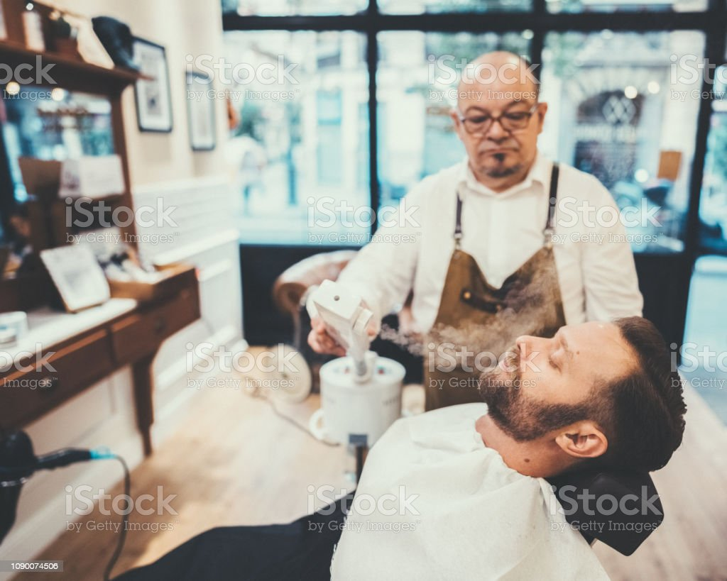 Barber Shaving Mans Beard In The Barber Shop Stock Photo - Download