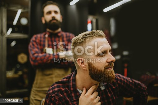 Good looking man visiting barber shop. Trendy and stylish beard styling and cut.