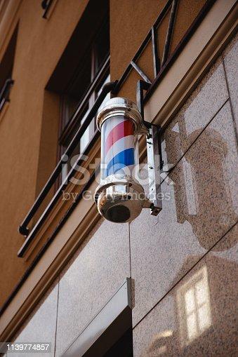 istock Barber Shop Pole. Symbol of a barbershop Lamp sign 1139774857