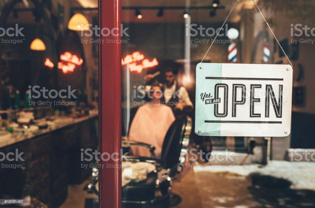 Barber skyltfönster med öppen underteckna och barber arbetar inomhus bildbanksfoto