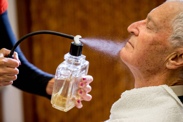 Barber Spraying Aftershave on Senior Man Barber Spraying Aftershave on Senior Man's Face shaving brush shaving cream razor old fashioned stock pictures, royalty-free photos & images