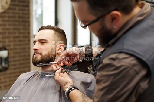986804130istockphoto Barber styling beard with scissors to client at barbershop 840457654