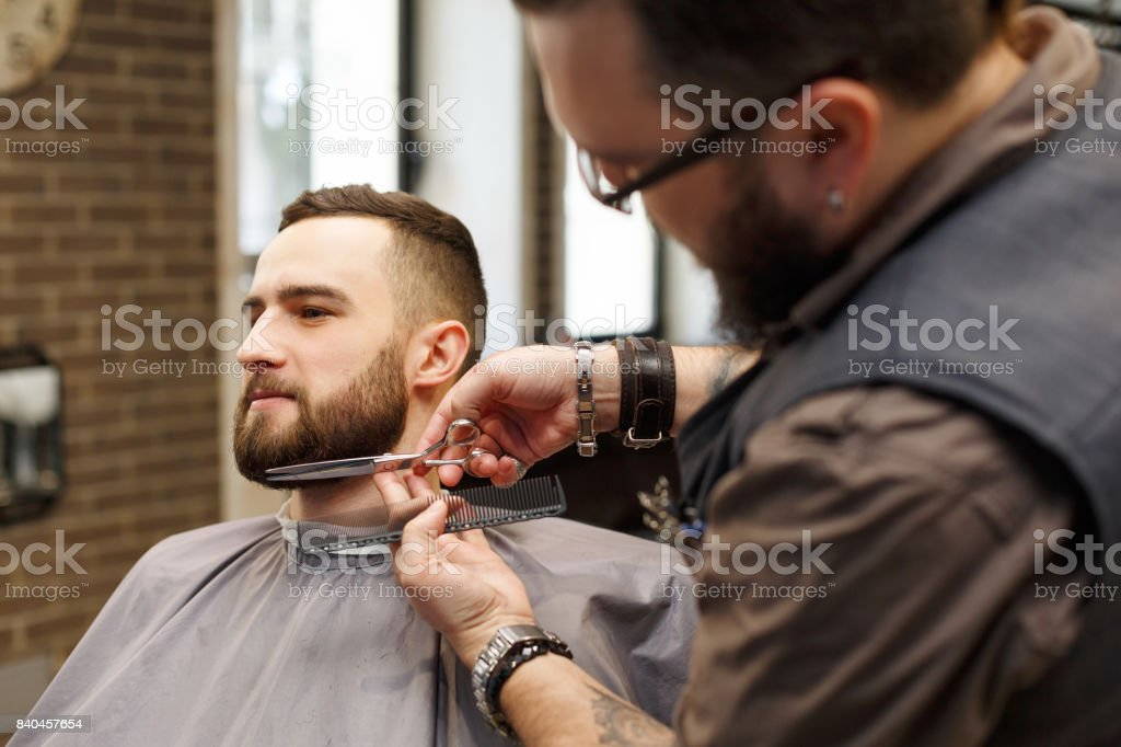 Barber styling beard with scissors to client at barbershop - fotografia de stock