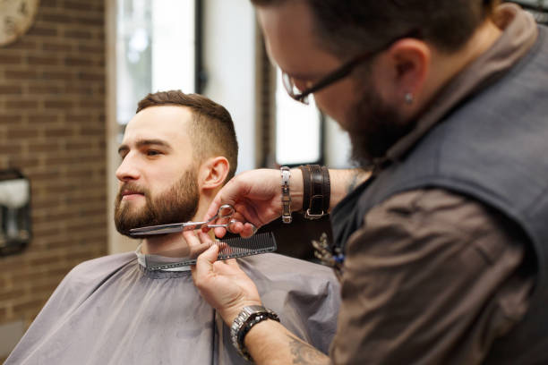 barber styling beard with scissors to client at barbershop - beard stock pictures, royalty-free photos & images