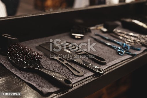 1131824191 istock photo Barber tool in barbershop. Hairdresser tool. Scissors, combs, razors, clippers. Tool for the wizard. Organization of the workplace. Selective focus. 1180883824