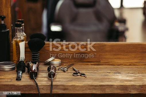 istock barber tools on wooden shelf and mirror in barbershop 1007175672