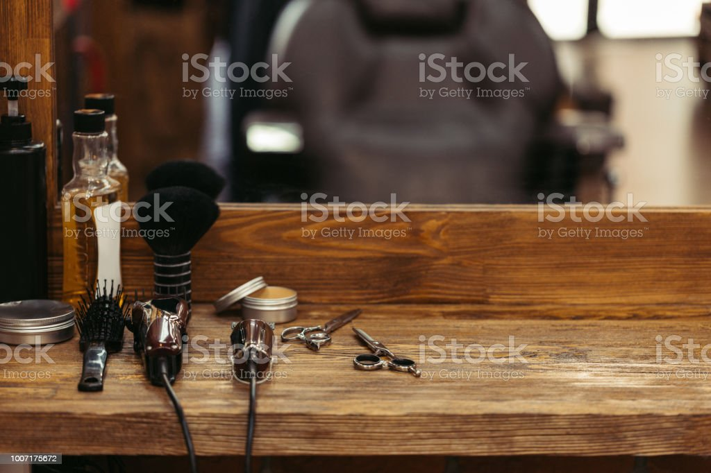 barber tools on wooden shelf and mirror in barbershop - fotografia de stock