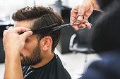 istock Barber using scissors and comb 640274128