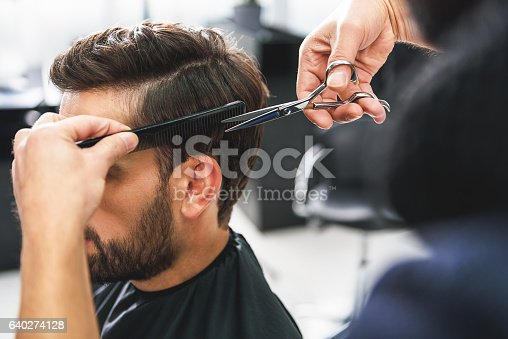 928445950 istock photo Barber using scissors and comb 640274128