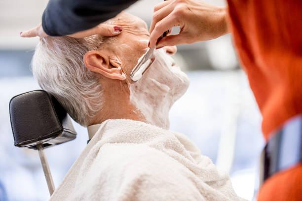 Barber Using Straight Razor to Shave Senior Man Barber Using Straight Razor to Shave Senior Man shaving brush shaving cream razor old fashioned stock pictures, royalty-free photos & images